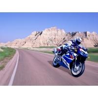 Мотоциклист мчится на большой скорости по пустой трассе, обои для рабочего стола